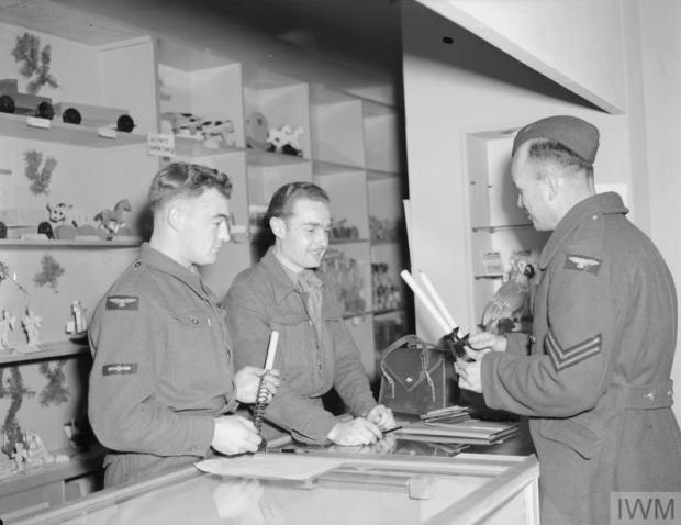 RAF CORPORAL S Peachey buys candlesticks made from metal salvaged from German military equipment in a British forces shop at Detmold. Behind the counter are (from the left) Leading Aircraftman J Browning, RAF and Aircraftman D F Payne, RAF. Image © IWM. IWM catalogue reference CL 3547. Original source https://www.iwm.org.uk/collections/item/object/205207498.